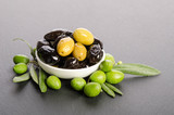 Black and green  olives  mixed in the  porcelain bowl on gray stone - 190537343