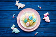 Easter bunny and easter eggs cookies. Sweets, pastry for Easter table. Blue wooden background top view