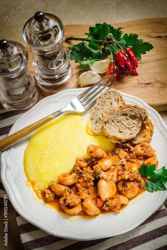 Fototapeta Stewed cuttlefish with polenta and crostini