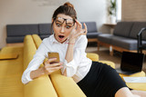 Young shocked business lady using mobile phone - 190548580