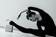 elegant beautiful modern ballet dancer girl with perfect body sits on the floor on on twine.
