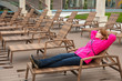 not a season for tanning.  girl in  jacket is lying on deckchair