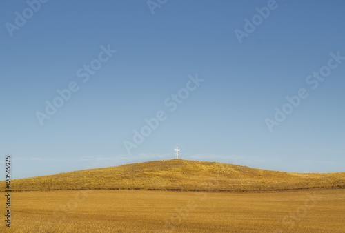 Foto op Aluminium Honing One small white wooden cross on a brown spring time hill under a blue sky in a deserted rural countryside