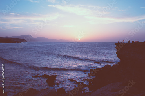 Fotobehang Strand Pink sunset at La Pared beach with people watching from the cliff, Fuerteventura, Canary Islands