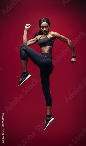 Slim and fit sporty woman jumping high