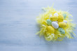 Colorful Easter Eggs in yellow feathers nest.
