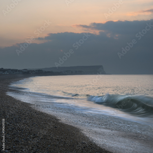 Fotobehang Bleke violet Beautiful vibrant sunrise beach landscape with waves breaking on beach