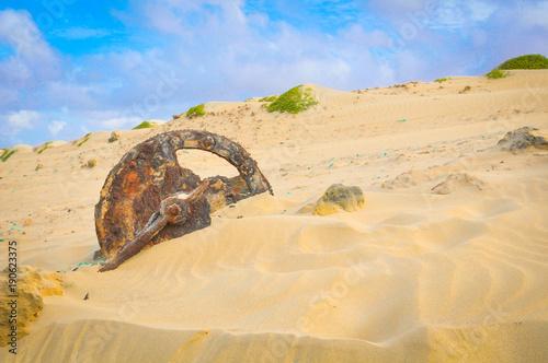 Staande foto Beige Desert landscape with rusty wheel