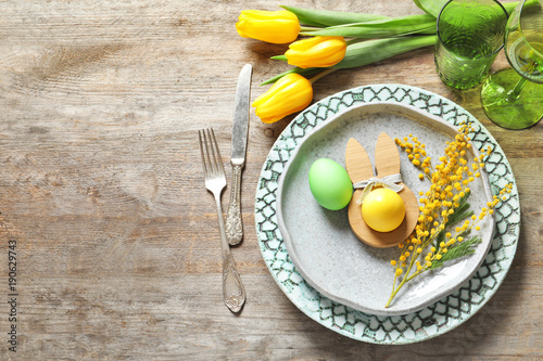 Beautiful festive Easter table setting with painted eggs and mimosa on wooden background - 190629743