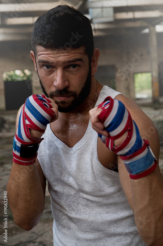 Portrait of muscular male boxer posing in boxing stance inside abandoned building.