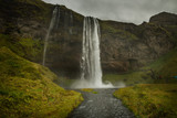 A powerful waterfall among the rocks covered with green moss. Iceland. Dark fabulous atmosphere, vintage.