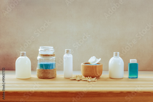 Papiers peints Spa Spa set of bottles with bath gel, shampoo, body milk and blue scrub with sea salt. Set standinh on wooden shelf on neutral background.