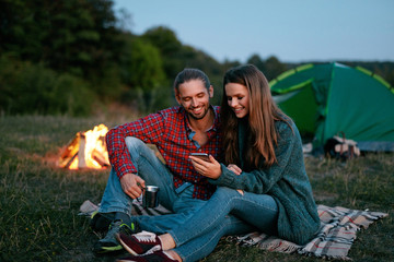 Tourist Couple In Love With Phone Near Camping In Nature