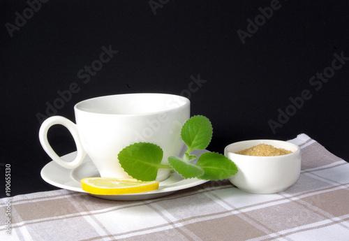 filiżanka herbaty z cytryną i miętą na tle obrusu