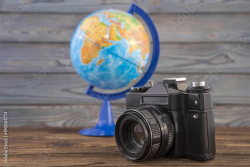 Foto Murales Concept travel, globe and vintage camera on a wooden background. Idea, photo tourism, adventure, travel around the world