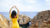 tropical woman with arms wide open feeling love on a cliff - 190669943