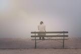 Anonyme junge Frau sitzt betrübt und einsam auf einer Bank im Nebel - 190670304