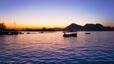 Timelapse of Fateh Sagar lake Udiapur India at dusk with boats and people. The timelapse of this popular tourist attraction shows people boarding for a boat ride at sunset and a jet ski tied on the - 190675999