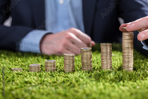 Businessperson Stacking Coins On Grass