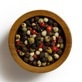Mixed peppercorns in dark wood bowl isolated on white from above.