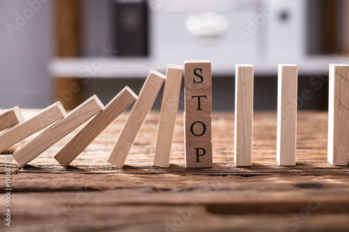 Falling Dominos Stopped By Wooden Blocks Showing Stop Text - 190687302