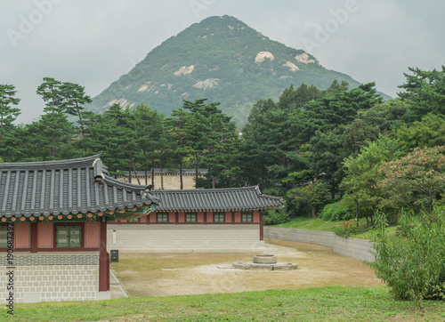 Fotobehang Seoel Partial view of old dwellings, trees and lawn, with a mountain rising in the background, at Gyeongbokgung Palace, Seoul, South Korea