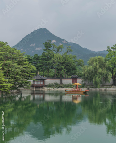 Fotobehang Seoel Man-made lake with a small boat, and a reflection of trees and a mountain, in Gyeongbokgung Palace, Seoul, South Korea