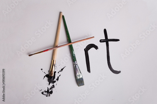 Art written in paint and paint brushes on canvas