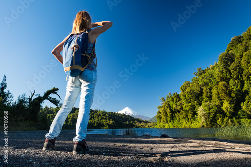Woman hiker enjoys volcano view from the coast of a lake