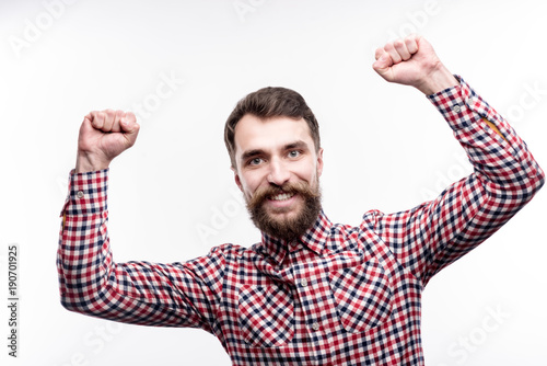 Fotobehang Kapsalon Long-awaited achievement. Charming bearded man raising his hands in triumph, having achieved success, and smiling brightly while posing isolated on a white background