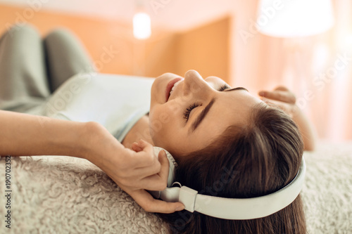 Fotobehang Muziek Relaxing song. The close up of a pretty teenage girl lying on the bed and listening to the music in the headphones while relaxing with closed eyes