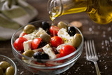 pouring virgin olive oil on vegetarian salad with fresh vegetables, feta and green olives. - 190702789