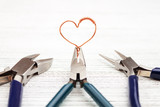 Jewelry tools on white background. Heart made of copper wire. Wire wrap