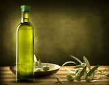 bottle of oil with olive branches on the wooden table - 190708941