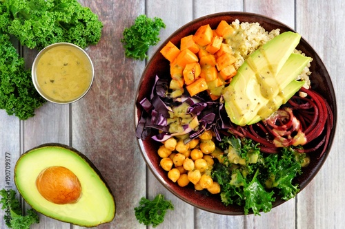 Buddha bowl with quinoa, avocado, chickpeas, vegetables on a wood background, Healthy eating concept. Overhead scene. - 190709377