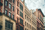 Row of vintage New York City apartment buildings in a variety of brick and brownstone facades - 190711399
