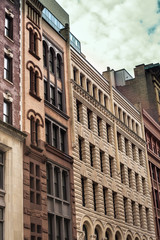 Row of vintage New York City apartment buildings in a variety of brick and brownstone facades