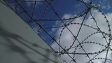 Concrete wall of the prison with barbed wire under high voltage. Elegant panning at an unusual angle. Dramatic video. - 190724186