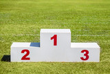 White wooden winner podium placed on green grass sport field on a sunny day