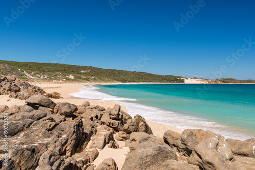 Desserted sandy beach with clear blue waters in summer