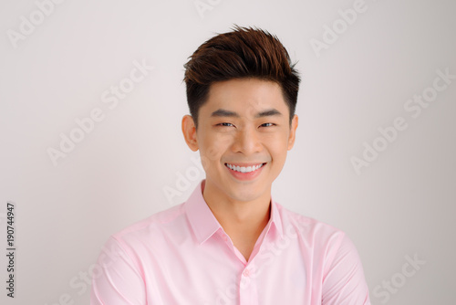 Handsome asian man stand and smile posing on gray background
