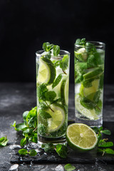 Mojito cocktail with lime and mint on black background