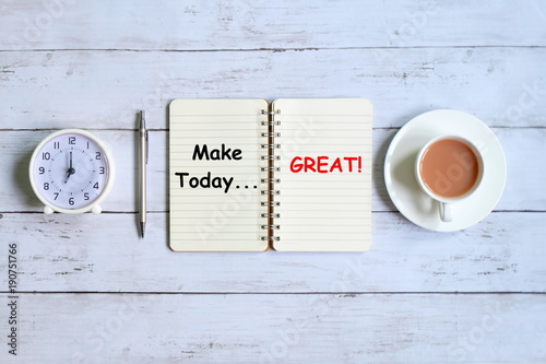 Papiers peints Positive Typography Top view of notebook written with 'MAKE TODAY GREAT!' with table clock pen and a cup of coffee on white wooden background.