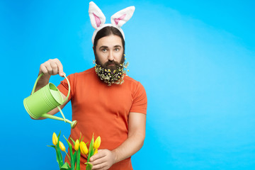 Happy Easter concept. Nice kind muscle man male with watering can watering spring's yellow tulips flowers isolated on blue background. Spring time concept