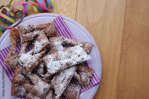 Italian carnival pastry on wooden background. Traditional chocolate Crostoli on a plate