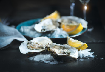 Fresh oysters close-up on blue plate, served table with oysters, lemon and champagne in restaurant. Gourmet food