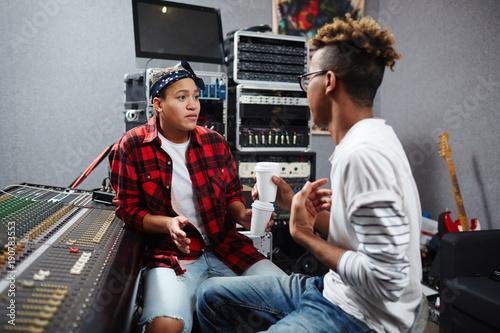 Two professional sound record operators having talk in audio studio