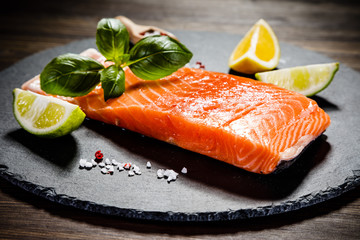 Fresh raw salmon fish served on black stone on wooden table