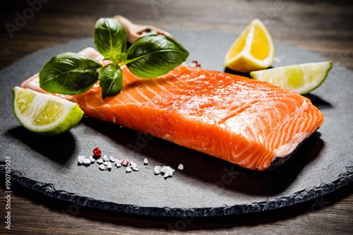 Papiers peints Steakhouse Fresh raw salmon fish served on black stone on wooden table