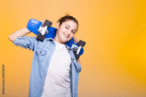 Fotobehang Skateboard Happy teenager girl with her blue skateboard on shoulders on yellow background